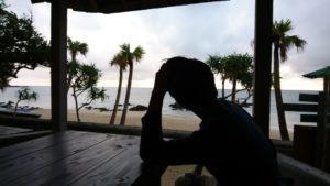 海を見てたそがれる男性